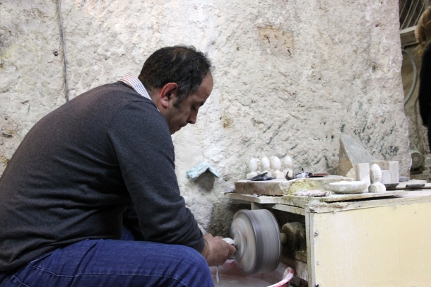A craftsman slowly polishing and smoothing stone into a decorative egg...or something like that.