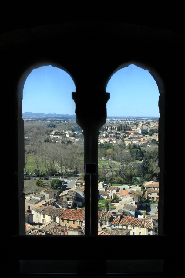 Arched windows look out over a sleepy town below on a sunny Sunday.