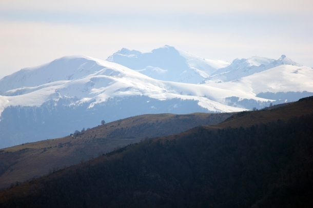 Hazy snow-covered mountains off in the distance from a hike around Foix.