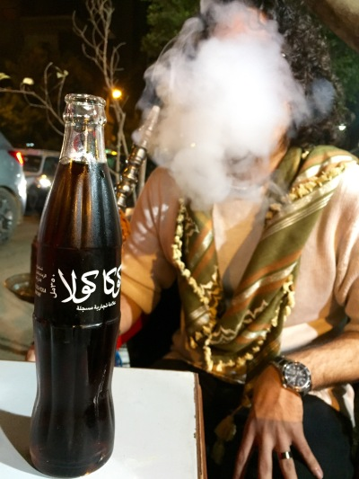 "You can still get plenty of oldschool glass bottles around here. That's ""Coca Cola"" in Arabic, by the way. And my coworker behind a cloud of shisha smoke."