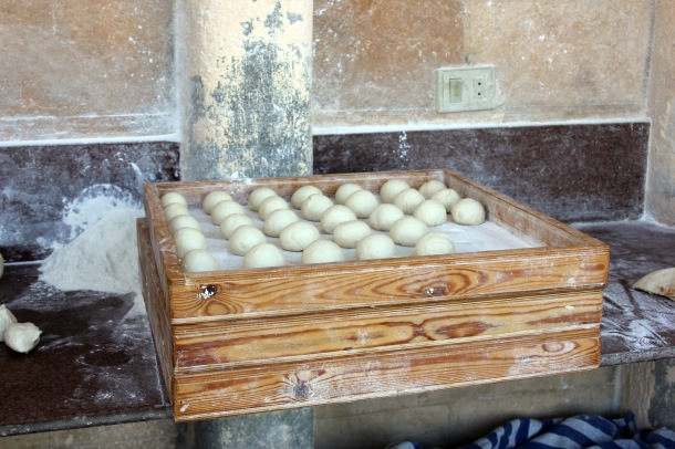 Fresh balls of bread dough waiting to be flattened and placed into a burning hot oven where they would puff up and become pita.